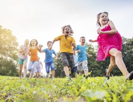 Low angle view of large group of little children having fun while running outdoors.
