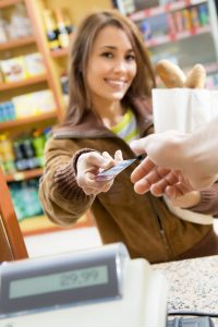 woman doing shopping in a grocery store and paying by credit card